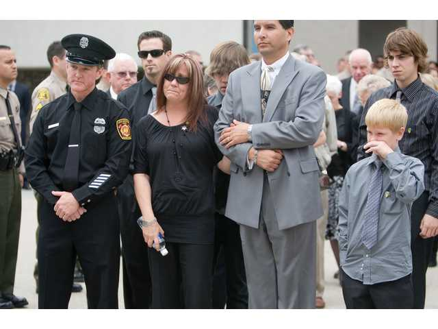 Family members of the late Deputy Randy Hamson, including his brother Tim, Randy's wife Cindy and her two young sons, Nicholas and Joshua, watch his casket as it is placed inside the hearse after the funeral service at Grace Baptist Church in Saugus Thursday morning. Hamson was laid to rest at Eternal Valley Memorial Park and Mortuary in Newhall.