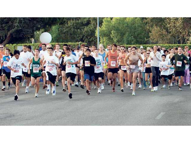 More than 250 runners race off the starting line in the Kiwanis 18th annual 5K run on Sunday morning. Saugus Olympian Allyson Felix, center right in black pants, was the Honorary Chair of the event,  which was a collaboration between the Kiwanis and the SCV Senior Center.