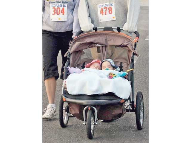 Kyden and Kenzie Ambrose, 6-month-old twins, are pushed by their parents, Jennifer and Zach, during the race.