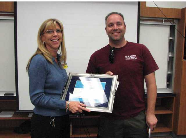 Wal-Mart Manager Shiela Finerty presents Zach Ambrose with a 2008 Teacher of the Year award at Saugus High School's October faculty meeting.