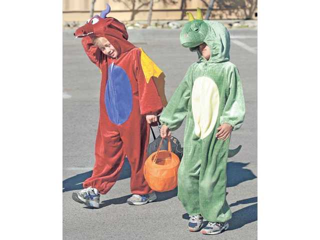 "Seven-year-old twins Raymond, left, and Jessica Furr dressed as a dragon and dinosaur for the Halloween costume competition at the ""Trick Or Trunk"" event at Richard Rioux Park in Stevenson Ranch on Saturday."