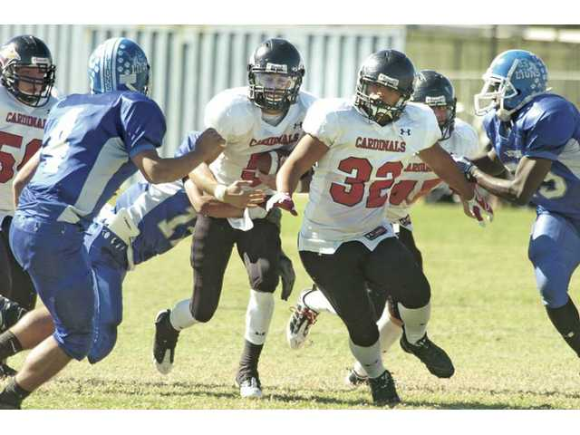 SCCS' Colin Mayhugh (5) follows Adrian Mosley (32) as they run against L.A. Lutheran on Saturday at First Lutheran High School. The Cardinals won 54-6.