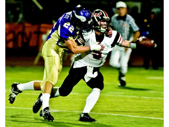 Spencer Buckley of Valencia, left,brings down Hart quarterback Spenser Souza, causing him to fumble in the first quarter.