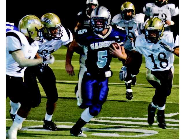 Saugus running back Ryan Zirbel takes off with three Golden Valley Grizzlies in hot pursuit, including defensive end J.P. Pinjanthuk (18). The Centurions won easily, 42-7, to remain unbeaten in the Foothill League.
