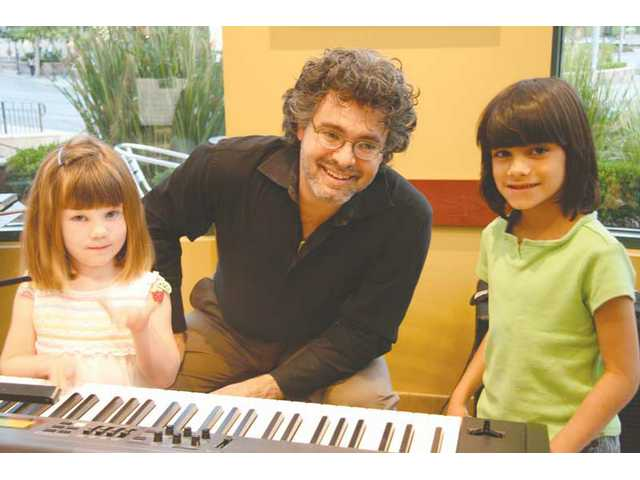 "Bryan Pezzone shares the piano with two participants at a Santa Clarita Symphony-sponsored ""Instrument Petting Zoo"" event, held at Borders in Valencia the first Friday of every month."