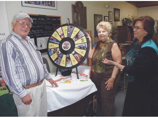 (Above) During Los Angeles County Dept. of Public Health Public Health Awareness Day in April, JoAnna Levinson, a public health nurse, (right) brought in an L.A. County Dept. of Health spinning wheel that describes the numerous free services available to the community.  Seen with Levinson are SCV Senior Center attendees Roland Anderson and Zandra Cousins. The event was coordinated through the SCV Senior Center's Health & Wellness program.