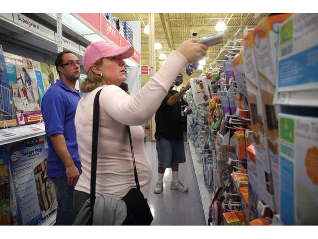 """Parents-to-be Christina and Jason Bobby, of Valencia, tag necessary items for their baby registry at Babies """"R"""" Us Saturday afternoon during the Canyon Country store's opening day."""