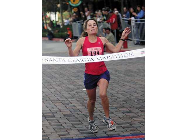 Ventura's Mary Jones crosses the finish line to win the women's version of the City of Santa Clarita Marathon on Sunday morning.