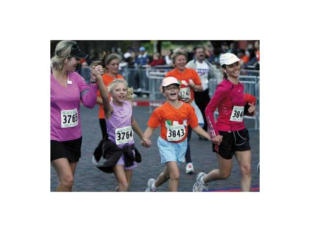 Connie Fitzpatrick of Valencia, left, and her daughter, Kassidy, 8, cross the finish line with friends Claire Pida, 8, and her mother, Erica, during the 5k event at the marathon.