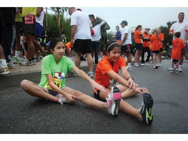 Twin sisters Chelsey and Weslie Totten, 13, of Newhall, stretch prior to running the 5K Sunday morning, part of the city's 13th annual Santa Clarita Marathon events. This is the second year the sisters have participated.