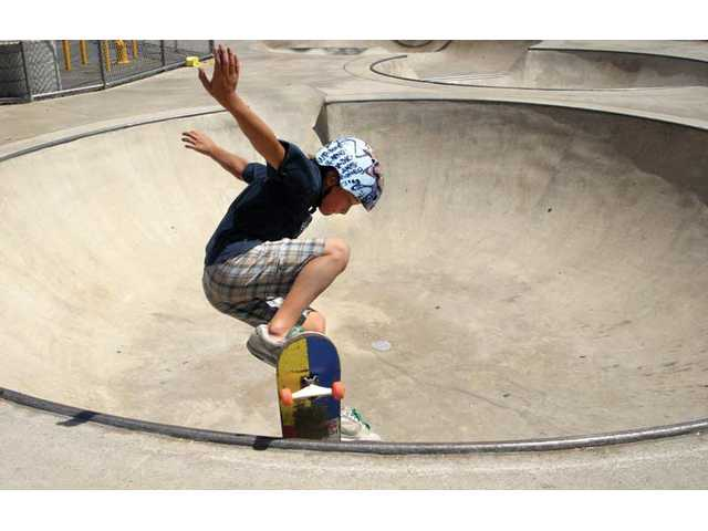 A local skateboarder grinds the lip of a bowl at the Santa Clarita skate park in this Augusr 2006 photo.