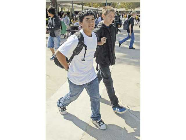 Placerita Junior High students Alex Guerrero, left, and Anthony Tohill walk toward the lunch table where Alex helped Anthony dislodge a piece of chicken from his throat.