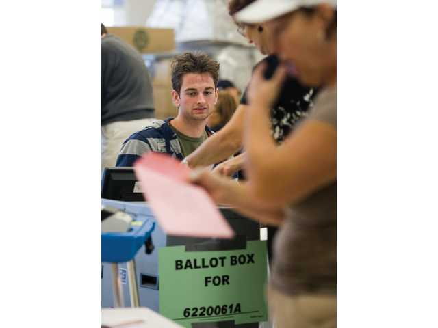 Canyon High School senior Nathan Cleveland works the polls at Skyblue Mesa Elementary School Tuesday morning. Cleveland got paid as well as earn extra credit for his government class.