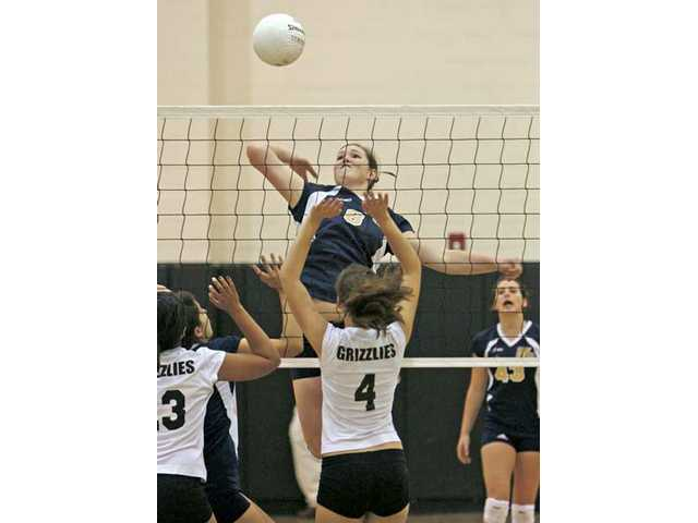 Wildcats middle blocker Courtney Cessna (8) swings at a ball during Tuesday night's 3-0 victory over Golden Valley at West Ranch High School.