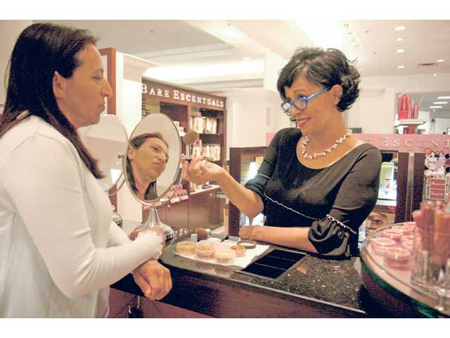 Patricia Quateman, business manager at 'Bare Escentuals,' applies makeup to Lancaster shopper Cecilia Serrano at Macy's on Monday morning. The store has added nearly 50,000 square feet of retail space, in time for the grand re-opening at 10 a.m. Saturday.