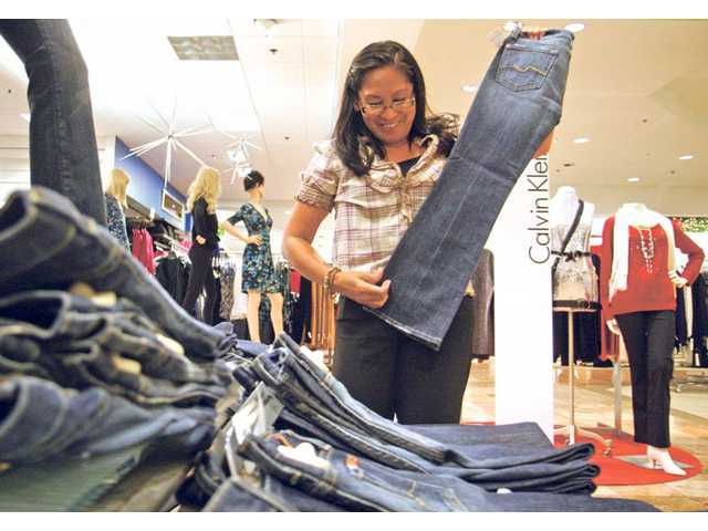 Merian Wakelin, Specialist at the Impulse department arranges her section of women's clothings at Macy's Monday morning. The newly expanded store will hold its grand re-opening on Saturday.