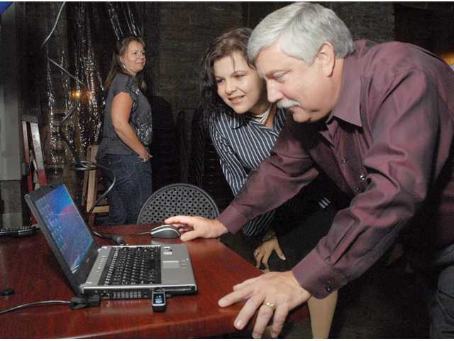 Hart Board candidate Linda Valdes and College of the Canyons board candidate Randy Moberg, right,  look at the early election returns on a laptop at their campaign party at Salt Creek Grille on Tuesday.