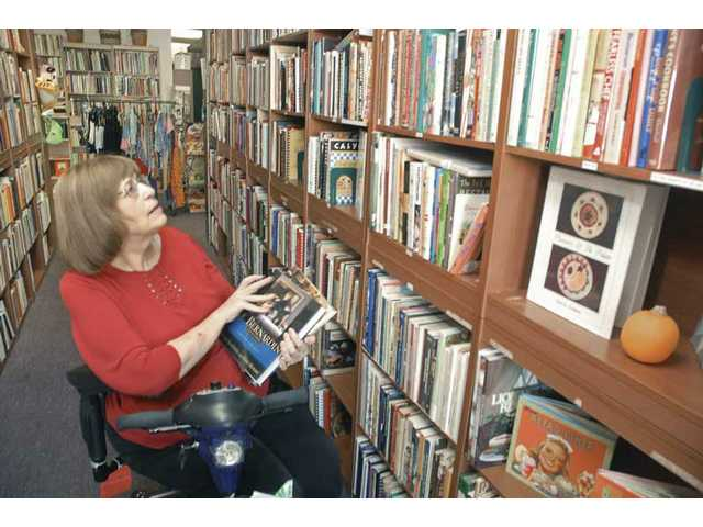 Mimi Hiller restocks the shelves at her store, Cookbooks Plus, in Newhall.