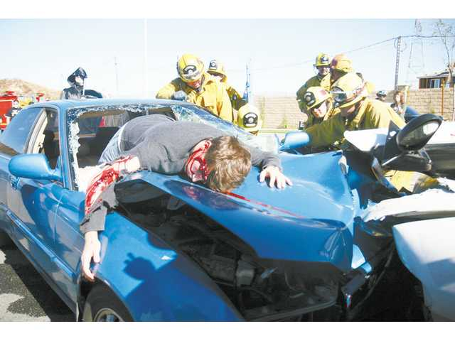 "Fire crews cooperate to pull out a ""crash victim"" during Golden Valley High School's Every 15 Minutes event Thursday afternoon."