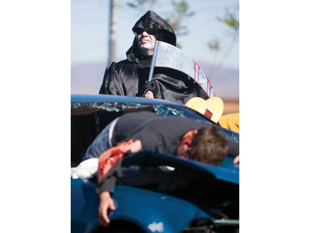 "The Grim Reaper, played by Los Angeles County Sheriff Deputy Wayne Waterman, stands over the simulated crash scene during the ""Every 15 Minutes"" event Thursday afternoon at Golden Valley High School."