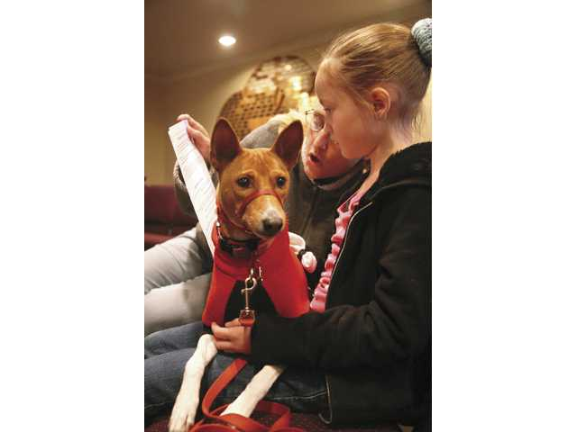 Christine Brown and eight-year-old daughter Erin Brown read a blessing together for their pet dog Pixie.