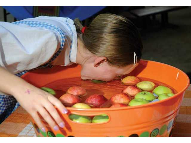 Dunking for apples was one of the most popular games at the Fall Festival sponsored by the First Presbyterian Church in Newhall.  The kids who successfully grabbed the apple did so by wedging the apple against the side of the tub.