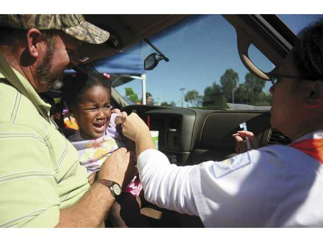 Castaic resident John Fast holds three-year-old daughter Abigail as she gets a flu shot from COC student nurse Zanaida Pelle early Friday afternoon.