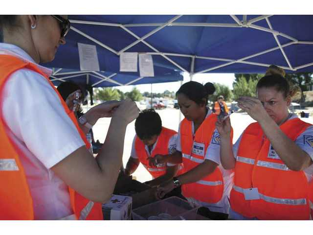 COC student nurses get vaccines ready during Friday's drive-through flu shot clinic.
