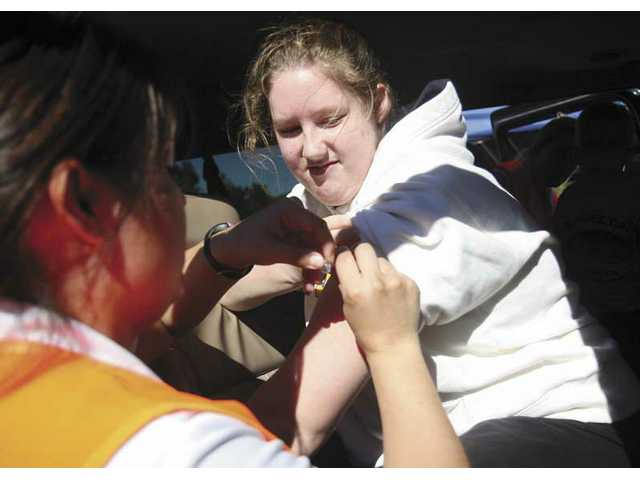 Castaic resident Rachel Fast, 18, gets a flu shot Friday afternon after she and six other family members drove through the free flu shot clinic at College of the Canyons.