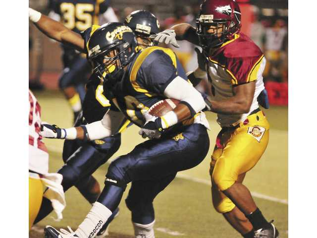 College of the Canyons running back Fred Winborn rushes against the Pasadena City College defense during first quarter action at COC on Saturday.