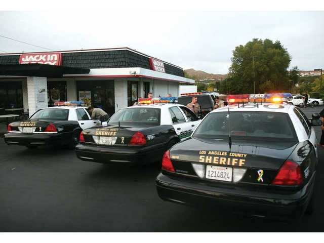 Sheriff deputies respond to a fight in the parking lot of the Canyon Country Jack in the Box on Soledad Canyon Road and Crossglade Avenue Saturday afternoon. Two alleged gang members were arrested.