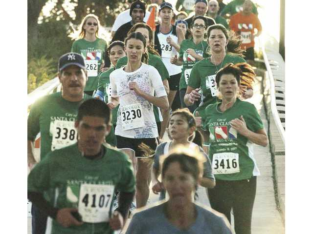 Participants in the 5K run come off the bridge over Magic Mountain Parkway as they head for the finish line.