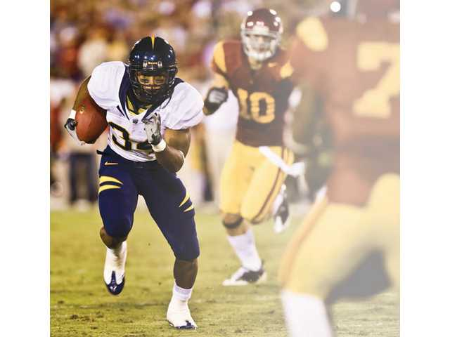 Valencia High graduate Shane Vereen (34) rushes the ball Saturday for Cal at the Los Angeles Coliseum against the University of Southern California.