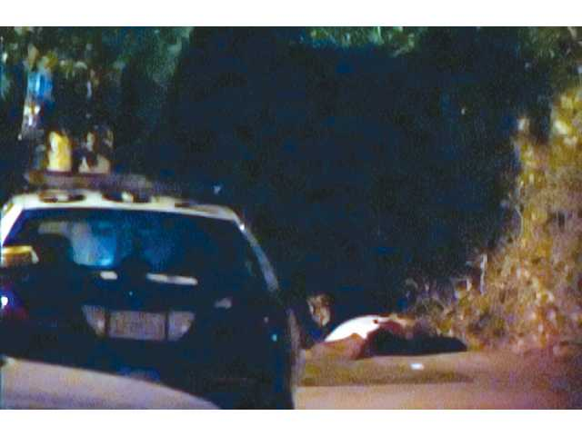 Dave Mendoza, 40, of Canyon Country, was found shot to death Sunday night in Mission Hills. In this still from a video recording, Mendoza's body can be seen lying next to a police cruiser.