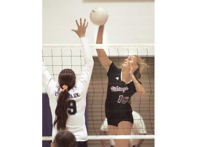Valencia's Sydney Striff (19) hits the ball as Villa Park's Mackenzie Calle  defends Tuesday at Valencia High.
