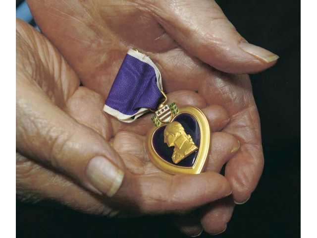 Donald Persens holds one of the three Purple Heart medals he received for injuries sustained while imprisoned in the Philippines.