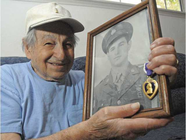 Donald Persens proudly displays a photo of him at the beginning of his service, along with one of this three Purple Heart Medals. Persens waited nearly 60 years to receive his medals.