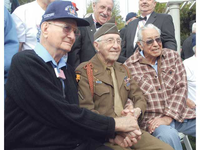 World War II Battle of the Bulge veterans, from left, Robert Watkins, 92, Tony Merincola, 92, and Cruz Carranza, 91, sit together as they pose for a photo at the third annual Veterans Day Ceremony held at Veterans Memorial Plaza in Newhall on Wednesday.