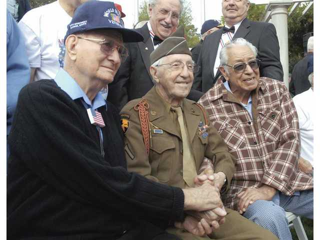 WWII Battle of the Bulge veterans (from left) Robert Watkins, Tony Marincola and Cruz Carranza sit together during Veterans Day ceremonies at Veterans Historical Plaza in Newhall on Wednesday.