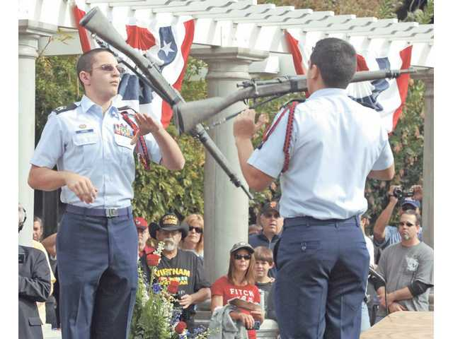 Valencia High School Junior ROTC members Patrick Dunkel, left, and Kelvin Ulloa give a rifle exhibition during the ceremonies.