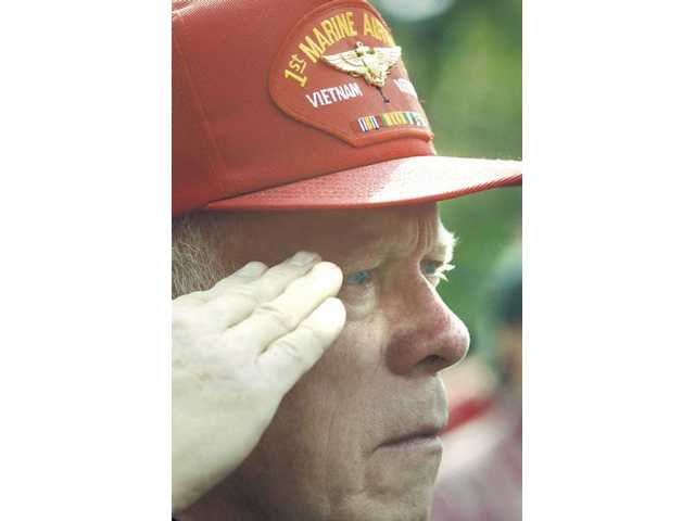 U.S. Marine Corps Vietnam veteran Robert Scobie salutes during the National Anthem opening Veterans Day ceremonies at Veterans Historical Plaza on Wednesday.