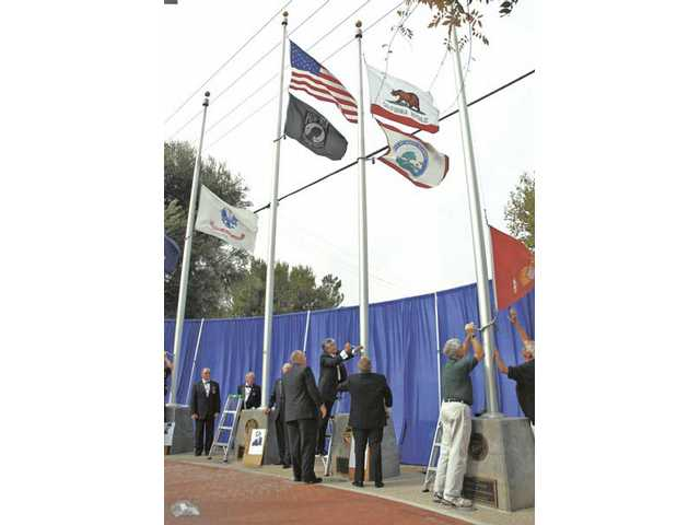 Flags are lowered and a new set are raised during the Changing of the Flags ceremony during the Veterans Day Program held at Veterans Historical Plaza in Newhall on Wednesday.
