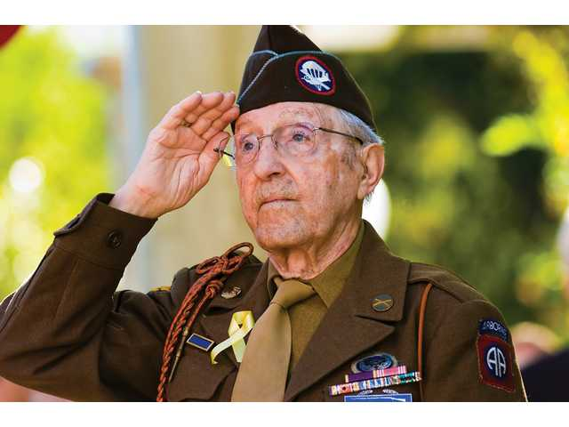 Tony Marincola, 91, who served in the 82nd Airborne in World War II and fought in the Battle of the Bulge, salutes the American flag as it is raised over the Veterans Historical Plaza in Newhall Tuesday morning.