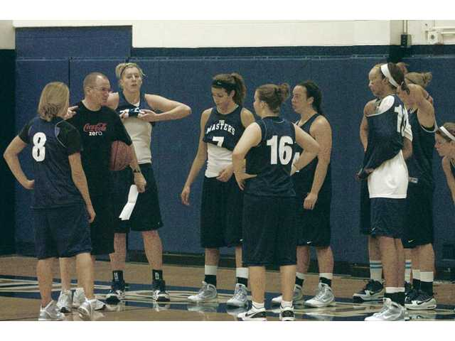 The Master's College women's basketball team listens to head coach Dan Waldeck during a break between drills at practice Wednesday in Bross Gym.