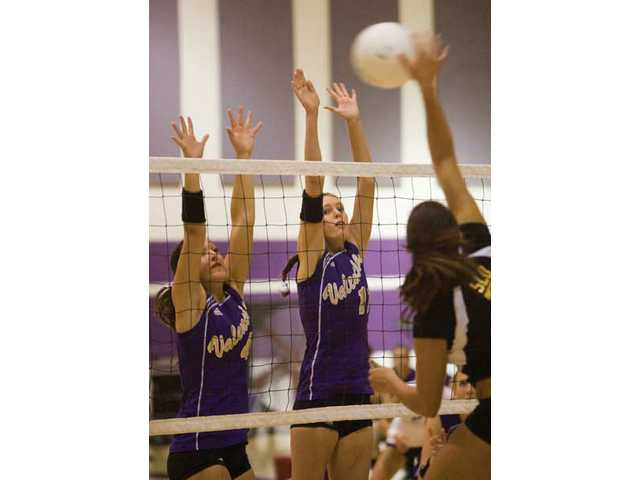 (Left to right) Kayla Hritz and Nicole Delange jump at the net in order to block a shot made by a San Luis Obispo opponent Tuesday.