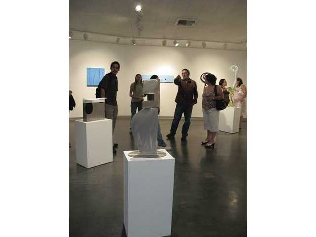 Visitors enjoy sculptures in the Art Gallery at College of the Canyons. The gallery is host to a variety of art exhibitions each year, and the next one, beginning Nov. 19, features works by cutting edge illustrators.
