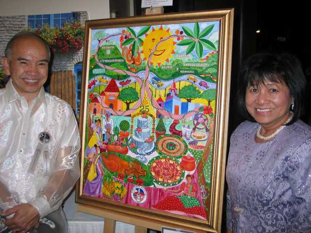 "Rhod and Evelyn Resella stand beside the ""Sharing Traditions and Enriching Traditions"" painting created by Evelyn . The painting tells the story of Filipinos in the Santa Clarita Valley, portraying oak trees, the city of Santa Clarita, Hyatt Valencia, Our Lady of Perpetual Help, traditional Filipino dishes and a three-layer anniversary cake."