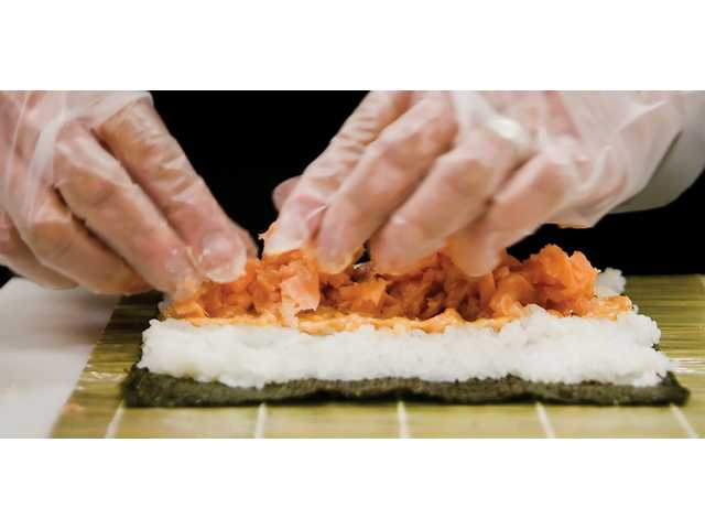 Robert Leon, sushi manager at Bristol Farms, prepares a spicy salmon roll Wednesday afternoon.