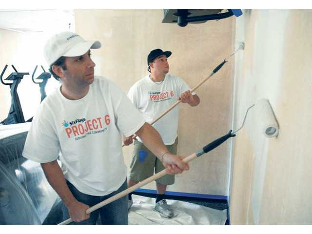 "Six Flags Magic Mountain employees Brandon Drake and Shaun Denes paint the walls of an exercise room at the Santa Clarita YMCA in Valencia on Friday as part of the ""Project 6"" Day of Service program."