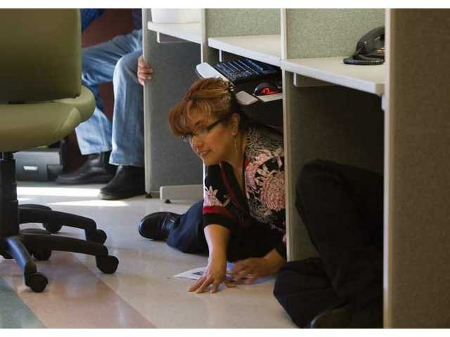 Maria Urrustieta, housekeeping supervisor at Henry Mayo Memorial Hospital, takes cover during the Great Shake Out event at the hospital Thursday morning.